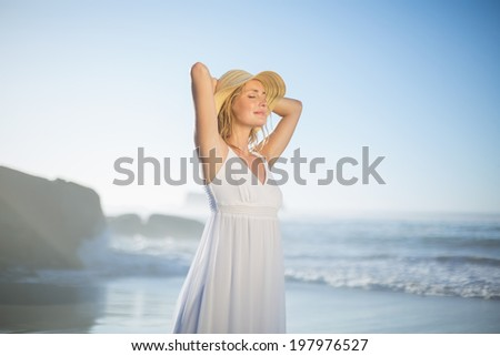 Smiling blonde standing at the beach in white sundress and sunhat on a sunny day - stock photo