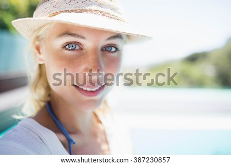 Smiling blonde with white hat looking at the camera - stock photo