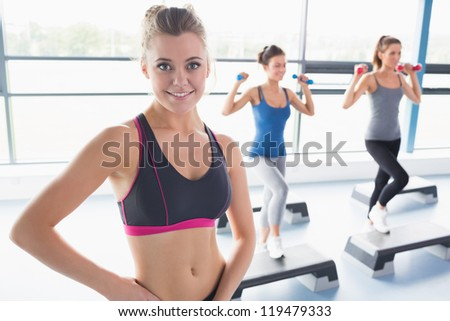 Smiling blonde woman at aerobics class in gym - stock photo
