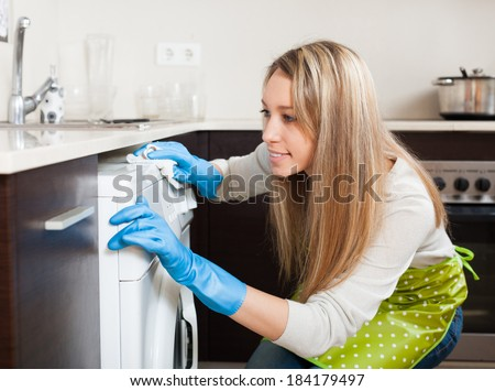 Smiling blonde woman cleaning washing machine at home kitchen - stock photo