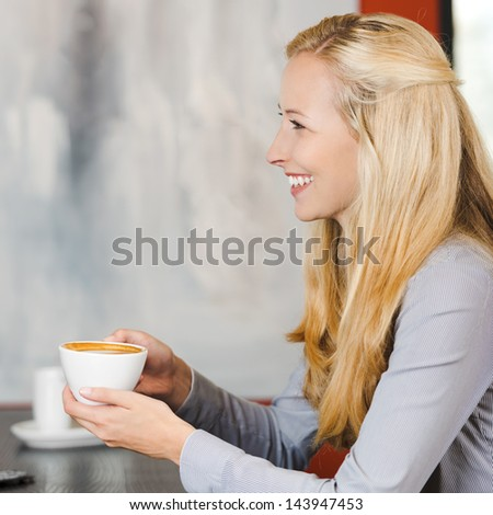 smiling blonde woman enjoying cappuccino at cafe - stock photo