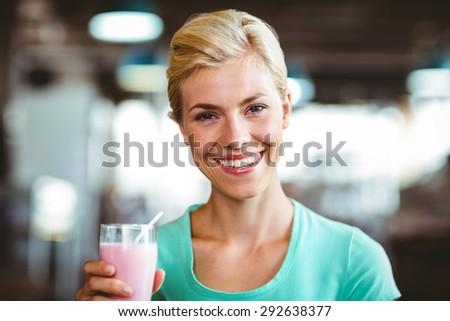 Smiling blonde woman enjoying her milkshake at the coffee - stock photo