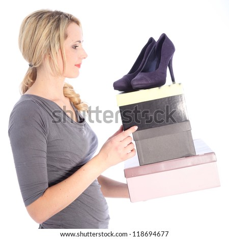 Smiling blonde woman holding high heels and shoe boxes on white background side view - stock photo