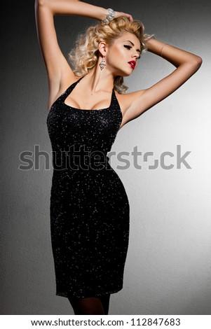 smiling blonde woman in black dress - stock photo