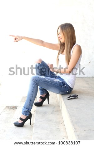 Smiling blonde woman pointing at someone - stock photo