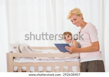 Smiling blonde woman with his son using digital tablet at home in bedroom - stock photo