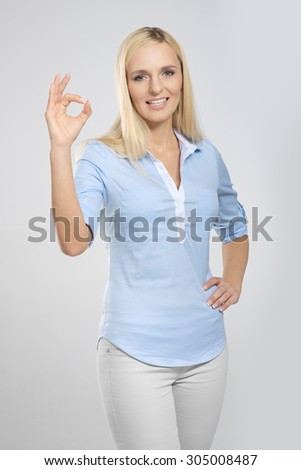 Smiling blonde woman with okay gesture - stock photo
