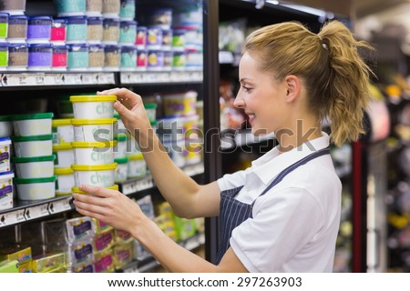 Smiling blonde worker taking a products in shelf in supermarket - stock photo