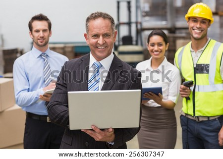 Smiling boss using laptop in front of his employees in a large warehouse - stock photo
