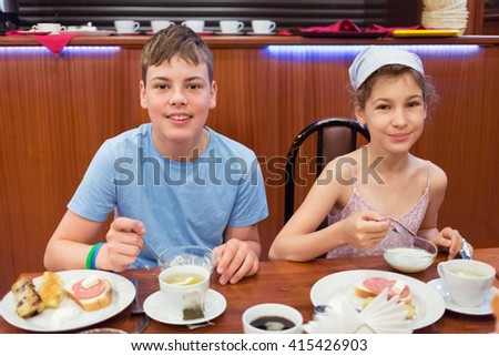 Smiling boy and girl have breakfast at table in small cafe. - stock photo