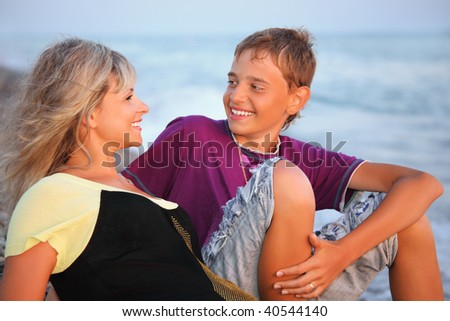 smiling boy and young woman on beach in evening, Looking against each other - stock photo