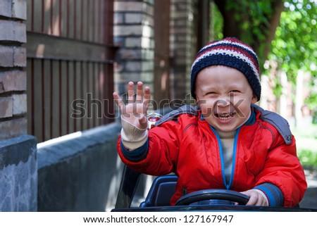 Smiling boy at the wheel toy electromobile - stock photo