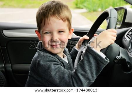 smiling boy driving car horizontal - stock photo