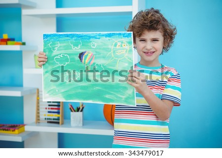 Smiling boy holding a picture beside a shelf - stock photo