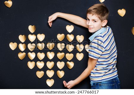 Smiling boy holding  golden heart on dark textured background - stock photo