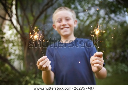 Smiling boy holding sparklers.  Focus on sparklers. - stock photo