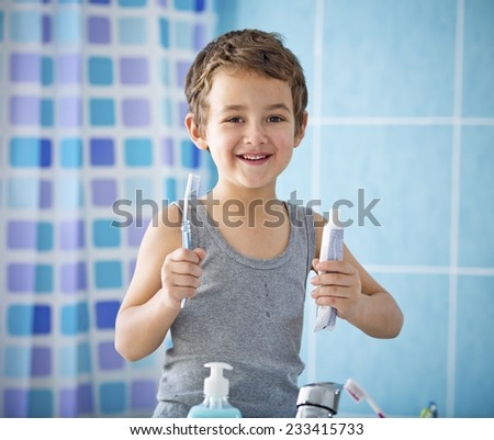 Smiling boy holding toothpaste and toothbrush after brushing his teeth  in the bathroom - stock photo