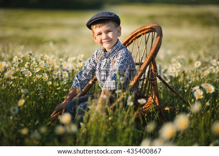 Smiling boy in a chamomile field sits in a rocking chair - stock photo