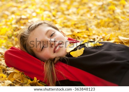 smiling boy in autumn leaves - stock photo