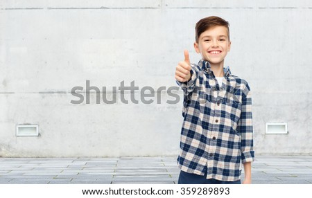 smiling boy in checkered shirt showing thumbs up - stock photo