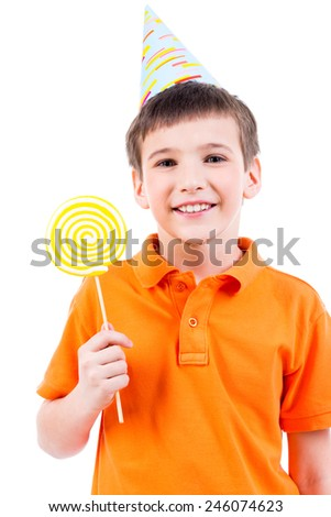 Smiling boy in orange t-shirt and party hat with colored candy - isolated on white. - stock photo