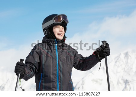 Smiling boy in ski suit against mountains and blue sky - stock photo