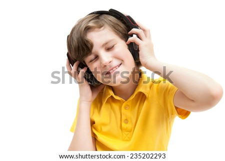 smiling boy in stereo-headphones listening to music, eyes closed - stock photo