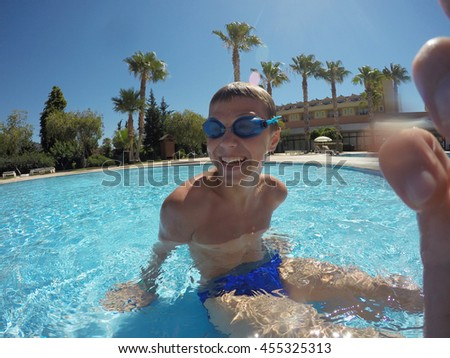 smiling boy in swimming pool - stock photo