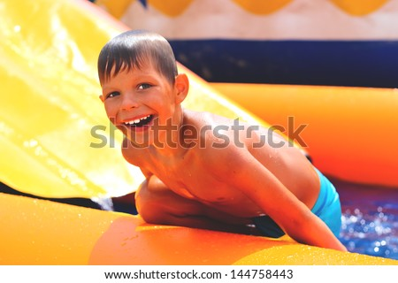 Smiling boy in the water near waterslide. - stock photo