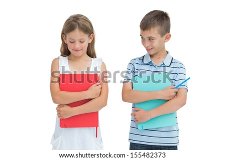 Smiling boy looking at his shy sister on white background - stock photo