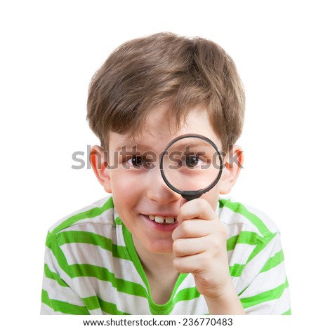 Smiling boy looking through a magnifying glass - stock photo