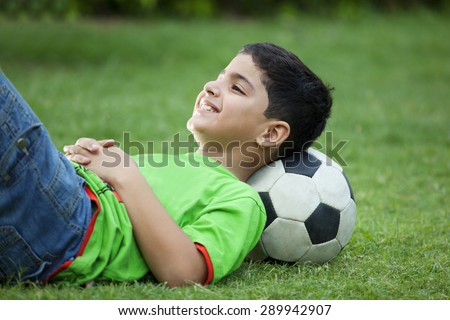 Smiling boy lying on grass with soccer ball - stock photo