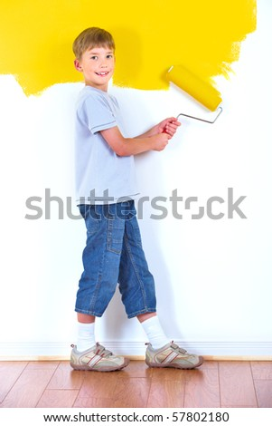 smiling boy painting interior wall of home. - stock photo