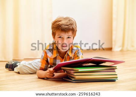 Smiling boy reading books at home.  - stock photo