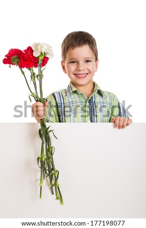 Smiling boy standing with empty blank and red carnations in hands, isolated on white - stock photo
