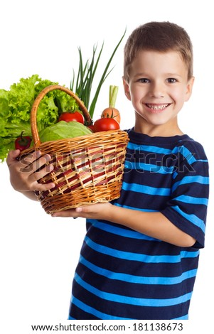 Smiling boy standing with fresh vegetables in the basket, isolated on white - stock photo
