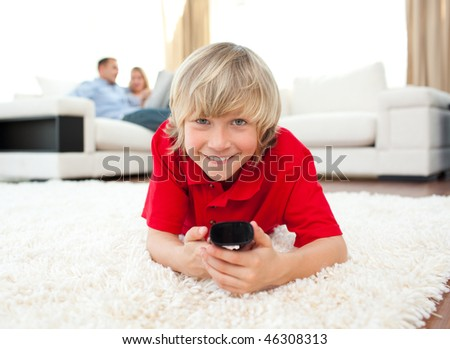 Smiling boy watching TV lying on the floor in the living-room - stock photo