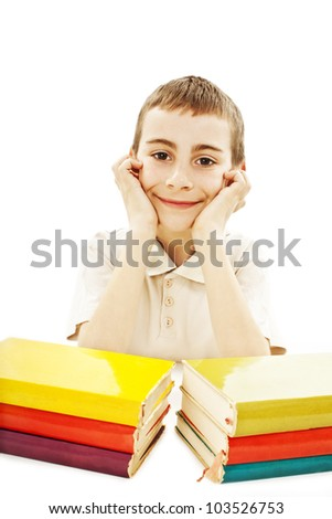 Smiling boy with colored school books on the table. Isolated on white background. - stock photo