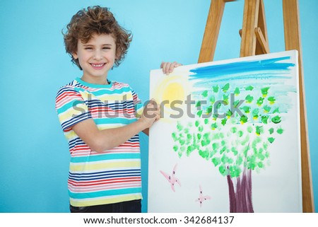 Smiling boy with his picture on an easel - stock photo