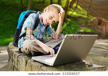 Smiling boy with laptop. - stock photo