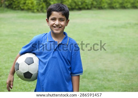 Smiling boy with soccer ball in park - stock photo
