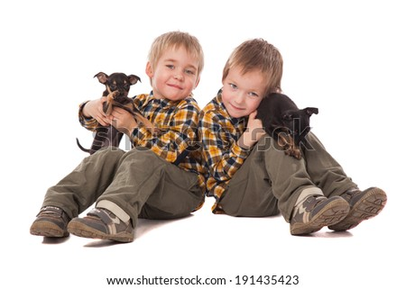 smiling boys holding puppies lie on the floor over white background - stock photo