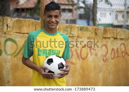 Smiling Brazilian teen wearing Brasil shirt posing for photo by rustic wall holding football soccer ball - stock photo