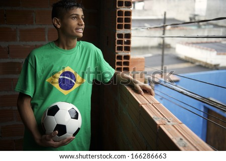Smiling Brazilian teen wearing Brazilian flag t-shirt stands holding football soccer ball looking out the favela window - stock photo