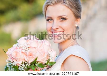Smiling bride holding big wedding bouquet - stock photo
