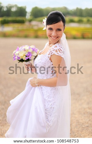 smiling bride on a walk in the park - stock photo