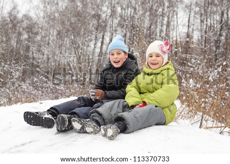 Smiling brother, sister seat on saucer in winter forest - stock photo