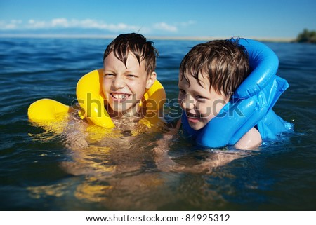 Smiling brothers swimming in the life jacket - stock photo