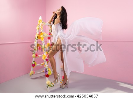 Smiling brunette beauty woman with flower ladder  - stock photo