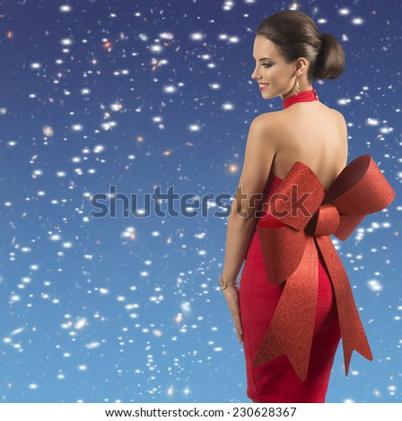 smiling brunette female posing with sexy red christmas dress and big glitter bow turned on her naked back, wearing golden jewellery  - stock photo